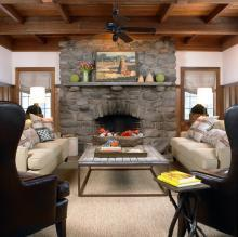 Modern Rustic Room with Stone Fireplace and Exposed Wooden Beams.